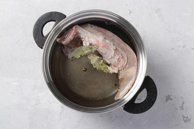 Langue de porc crue dans une casserole avec du poivre et du laurier