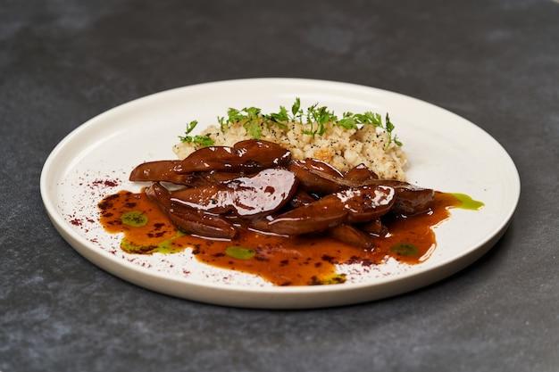 Langues d'agneau au four avec une bouillie de boulgour épicée dans une assiette blanche