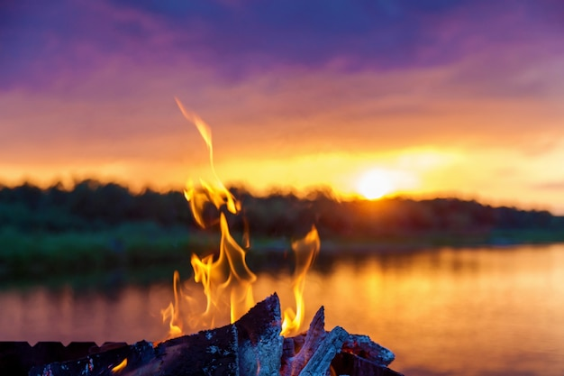 Langues de flammes rouges du feu près de la rivière au coucher du soleil.