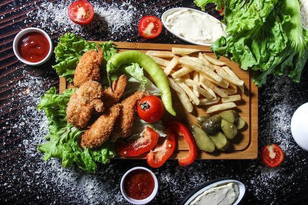 Lanières de poulet frites avec pommes de terre, herbes et cornichons