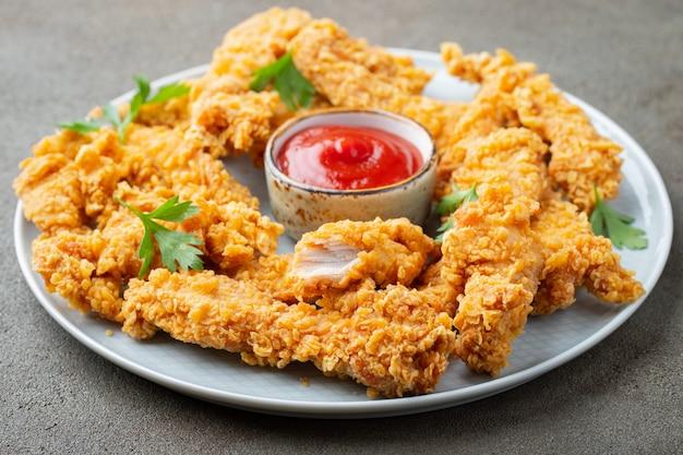 Lanières de poulet panées avec des sauces.