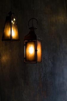 Lanterne accrocher devant la maison dans la nuit. lanternes noires en fer avec des verres sales brûlant