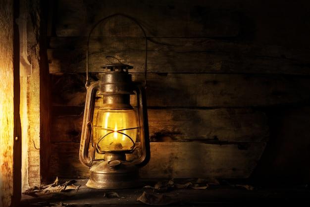 Lanterne ancienne au kérosène sur un vieux bois envahi par la végétation.