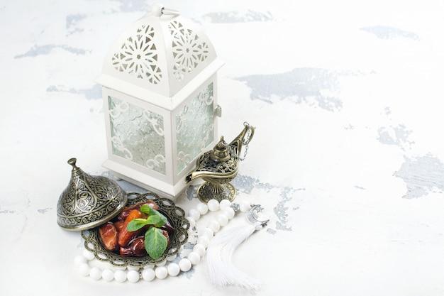 Lanterne arabe, dates, lampe aladdin et chapelet sur blanc
