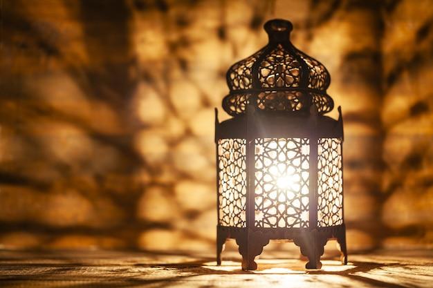 Lanterne arabe ornementale avec bougie allumée rougeoyante