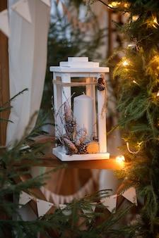 Lanterne blanche en bois avec des bougies décorées de cônes à côté de l'arbre de noël