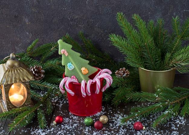 Lanterne avec une bougie, des cônes de bonbons dans un seau rouge, des branches d'épinette et des cônes