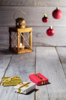 Lanterne avec une bougie et des décorations de noël - boules et boîtes sur une surface en bois blanche