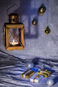 Lanterne avec une bougie et des décorations de noël sur fond argenté