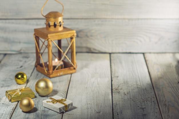 Lanterne avec une bougie et des décorations de noël sur une surface en bois blanche