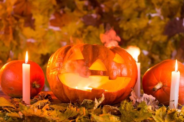 Lanterne citrouille d'halloween avec des feuilles sèches, des bougies et de la fumée.