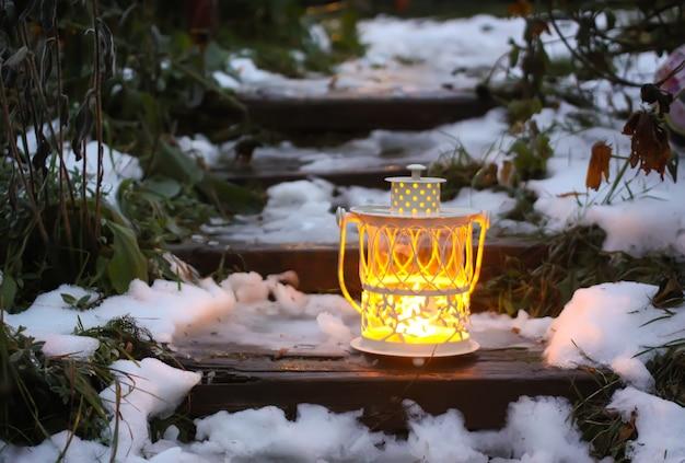 Lanterne décorative avec bougie allumée sur de vieux escaliers en bois dans le parc d'hiver le soir.