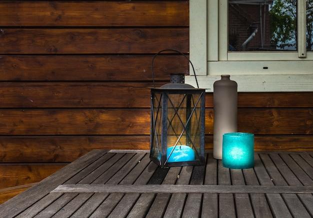 Lanterne décorative en métal avec des cannes bleues brillantes sur une table en bois, design élégant vintage avec espace de copie
