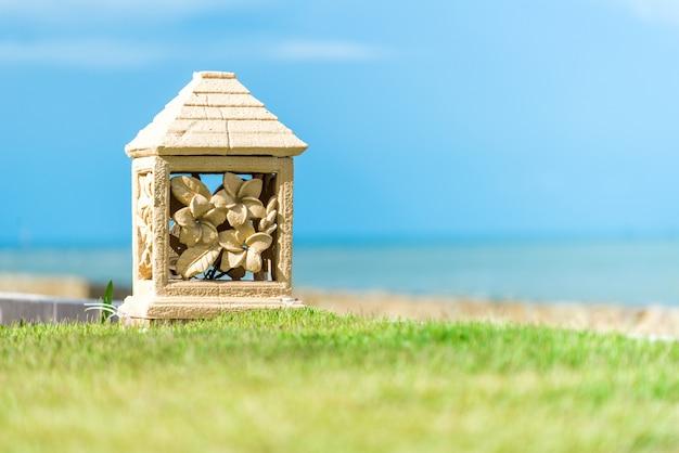 La lanterne est placée sur l'herbe près de la plage.