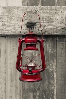Lanterne à huile style occidental, vieille lampe rouge style vintage accrocher sur du bois
