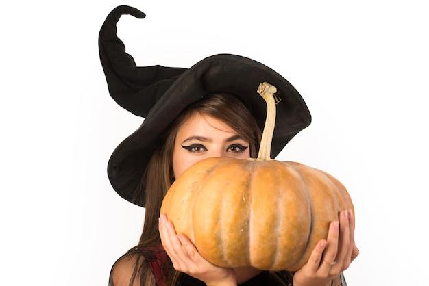 Lanterne jack tête de citrouille. des bonbons ou un sort. femme posant avec citrouille. belle jeune surprise
