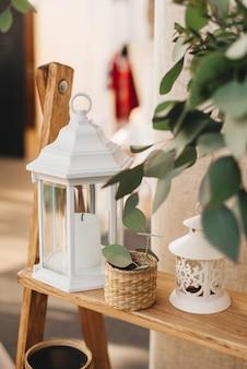 Lanterne en métal blanc pour bougies, ainsi que des éléments de décor rustique dans le décor d'un mariage ou d'une maison