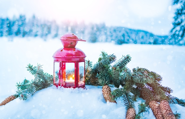 Lanterne de noël avec des branches de sapin sur la neige