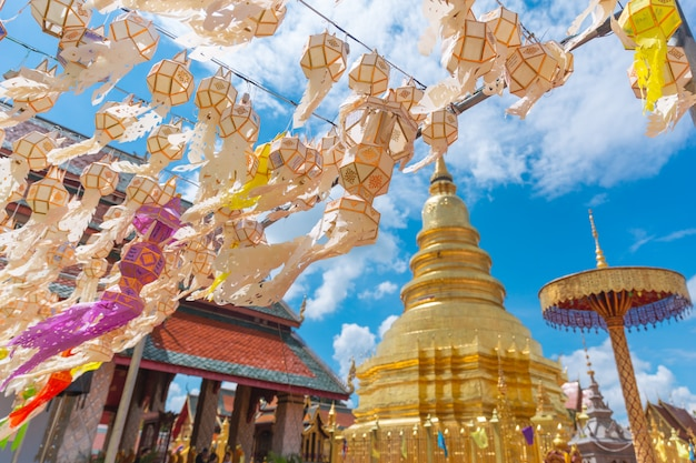 Lanterne en papier festival suspendu avec pagode d'or à wat phra that hariphunchai lamphun thaïlande