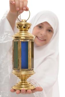 Lanterne de ramadan dans les mains de l'heureuse fille musulmane