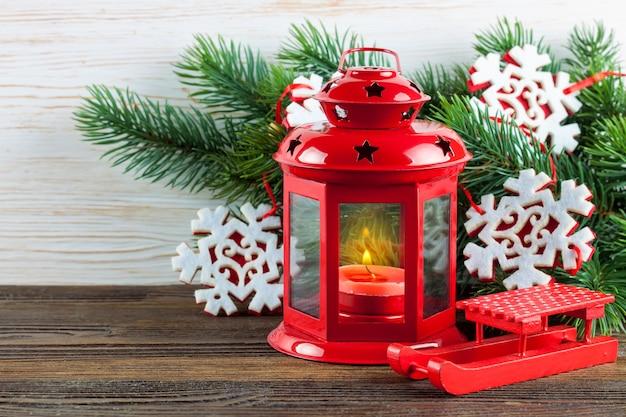 Lanterne rouge avec une bougie allumée et décoration de noël sur fond de bois blanc avec arbre de noël