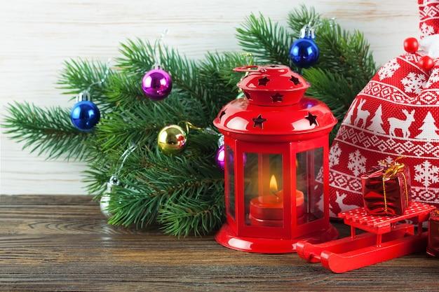 Lanterne rouge avec une bougie allumée et décoration de noël sur fond de bois blanc
