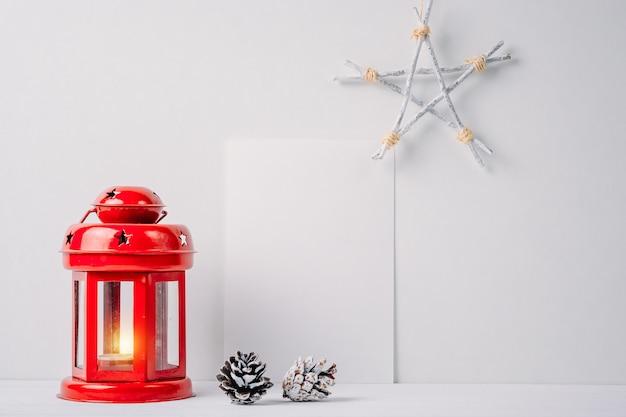 Lanterne rouge avec une bougie, des pommes de pin, une étoile et un drap blanc vide sur un fond blanc.