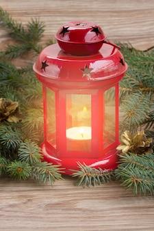 Lanterne rouge de noël avec bougie rougeoyante et arbre à feuilles persistantes et cônes