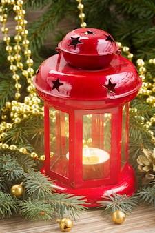 Lanterne rougeoyante de noël close up avec arbre à feuilles persistantes décoré