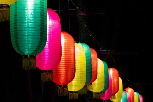 Des lanternes chinoises colorées pendent contre le ciel dans la nuit