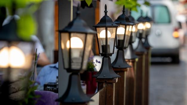 Lanternes décoratives le long de la barrière de café de rue.