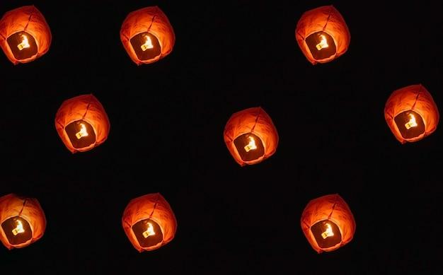 Lanternes en papier dans le ciel nocturne. a l'intérieur de la lanterne, le feu brûle en rouge. une belle tradition.