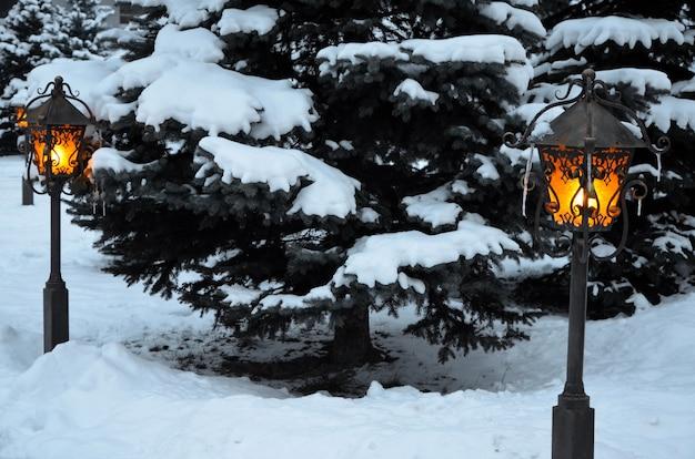 Lanternes rougeoyantes dans le parc avec la neige du nouvel an au crépuscule