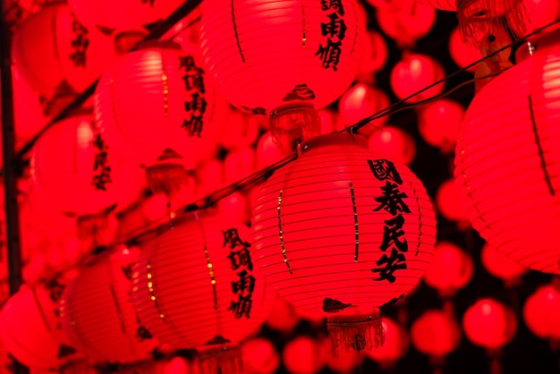 Lanternes rouges suspendues dans la nuit, les mots chinois sur lanterne signifient prier