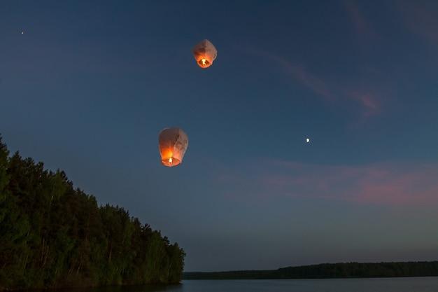 Lanternes volantes chinoises, survolant le lac dans l'obscurité