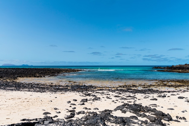 Lanzarote au pied d'immenses falaises volcaniques, depuis la plage de caleton blanco. le premier plan est dominé par un brise-vent courbe en pierre de lave immergé dans l'eau de mer bleu azur.