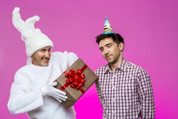 Lapin donnant un cadeau d'anniversaire à un homme ivre sur un mur violet.