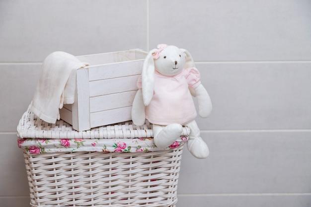 Lapin jouet blanc dans une robe rose est assis sur un panier à linge en osier dans une buanderie