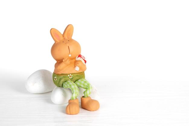 Le lapin de jouet en céramique décoratif se repose sur les pierres blanches