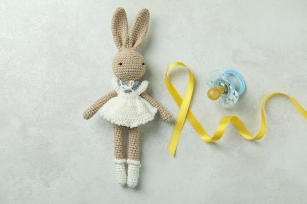 Lapin jouet, ruban de sensibilisation au cancer de l'enfant et sucette sur blanc