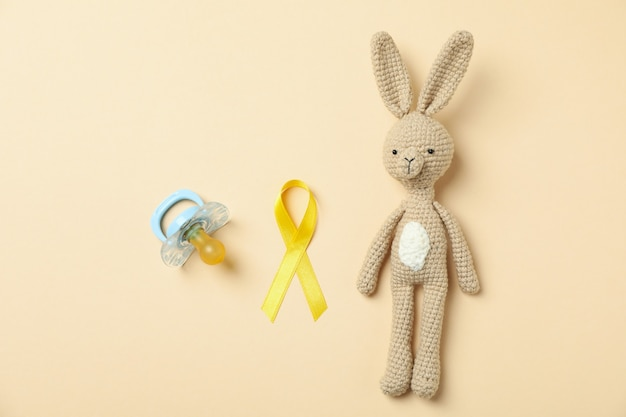 Lapin jouet, ruban de sensibilisation au cancer de l'enfant et sucette sur fond beige