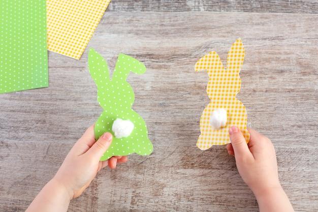Lapin en papier drôle avec les mains des enfants