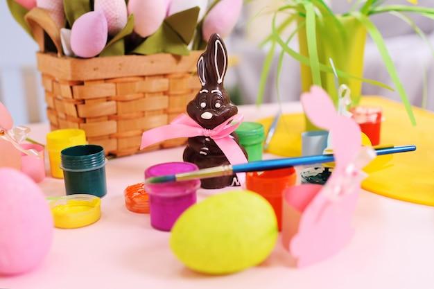 Lapin de pâques au chocolat à la surface du décor de pâques, fleurs, oeufs peints, boîtes de peinture.
