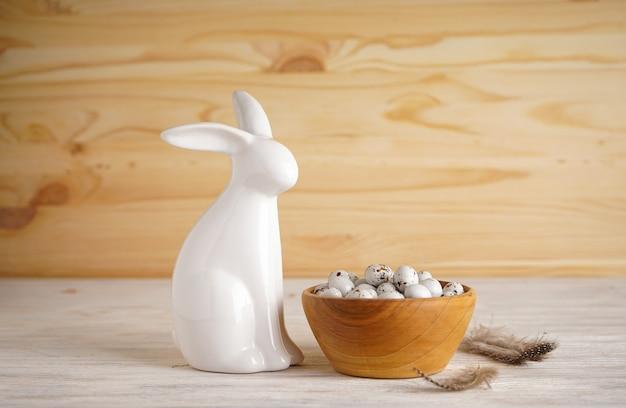 Lapin de pâques et oeufs de pâques dans un bol sur un fond en bois