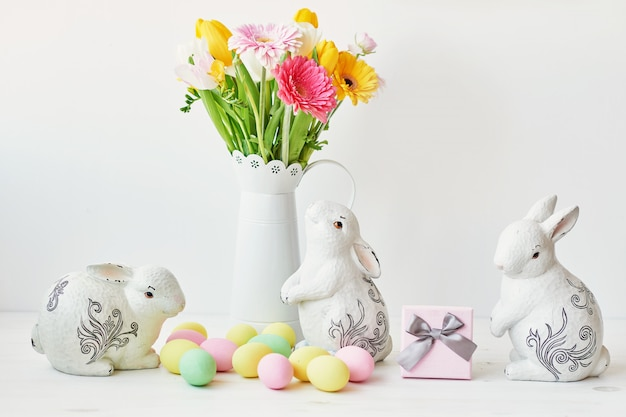 Lapin de pâques et oeufs de pâques sur la table de la cuisine. lapin blanc assis sur table avec bouquet de tulipes et crête et oeufs colorés.