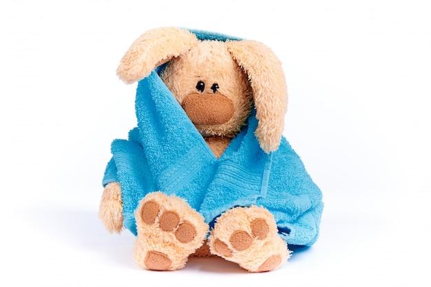 Lapin en peluche doux dans une serviette bleue