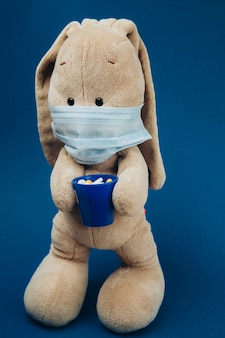 Le lapin en peluche porte un masque médical de protection.