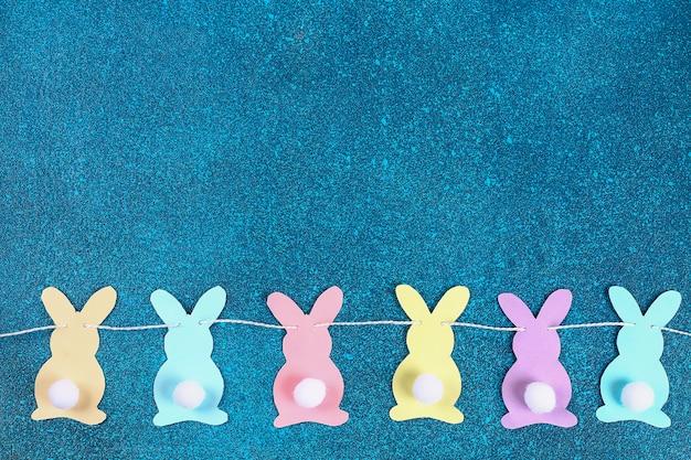 Les lapins de guirlande de pâques bricolage fait fond de papier bleu.