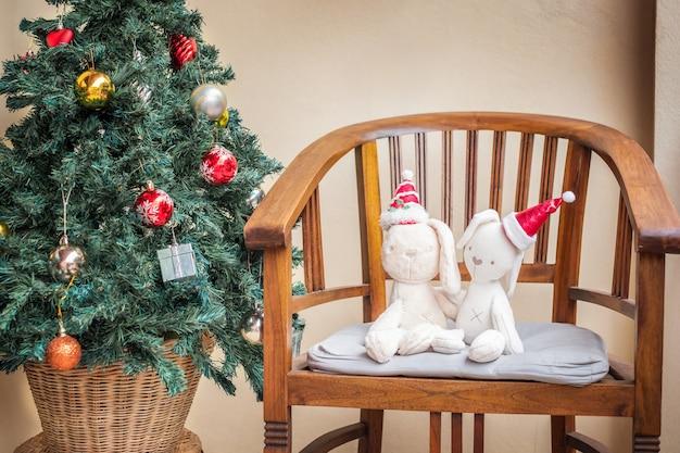 Lapins jouets dans la casquette de noël santa près de l'arbre de noël
