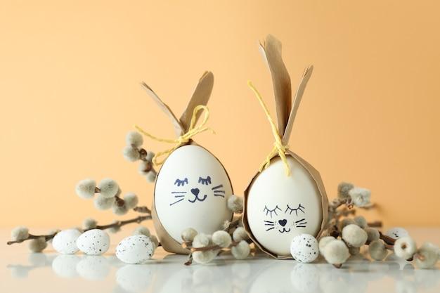 Lapins de pâques faits d'oeufs, oeufs de caille et chatons sur fond beige